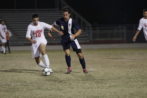 Sophomore Amine Benkirane dribbles the ball against Alonso. (Photo by Matt Lutton)