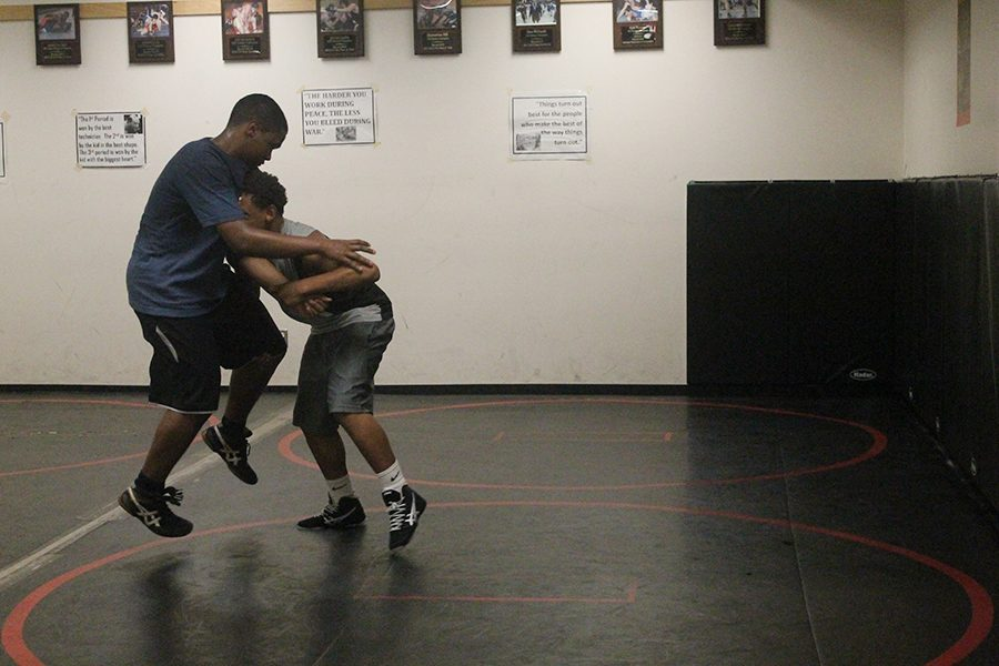 William Andrews and Dejohn Jones grapple  during a wrestling practice.  The team focuses on the fundamentals of take downs in most practices. (Photo by Lauren Komar)