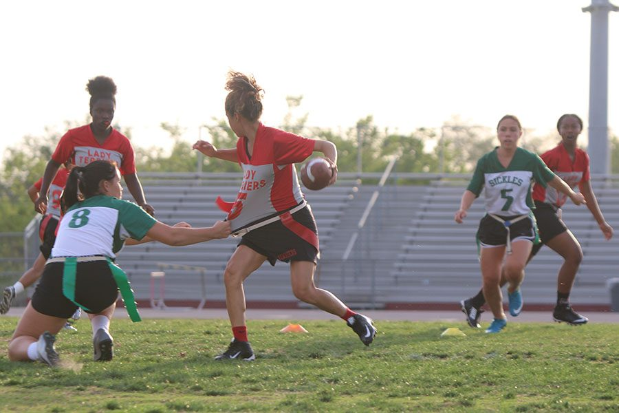 As her flag is pulled from her hip, Kathy Dinarte holds the ball and tries to run to the end zone.