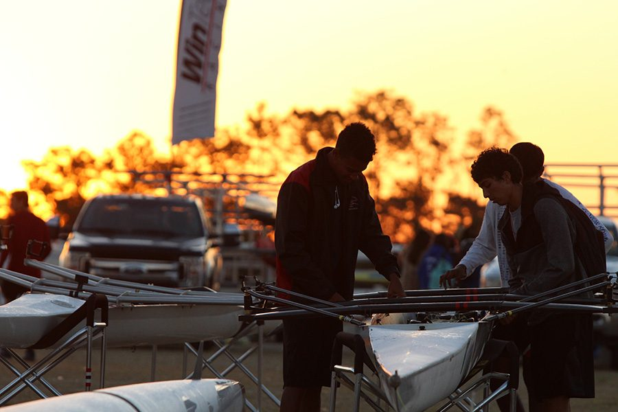 Savion Fordham (10) and Rafael Carrion (11) rigged a white quad the first morning of racing as the sun rose behind them.