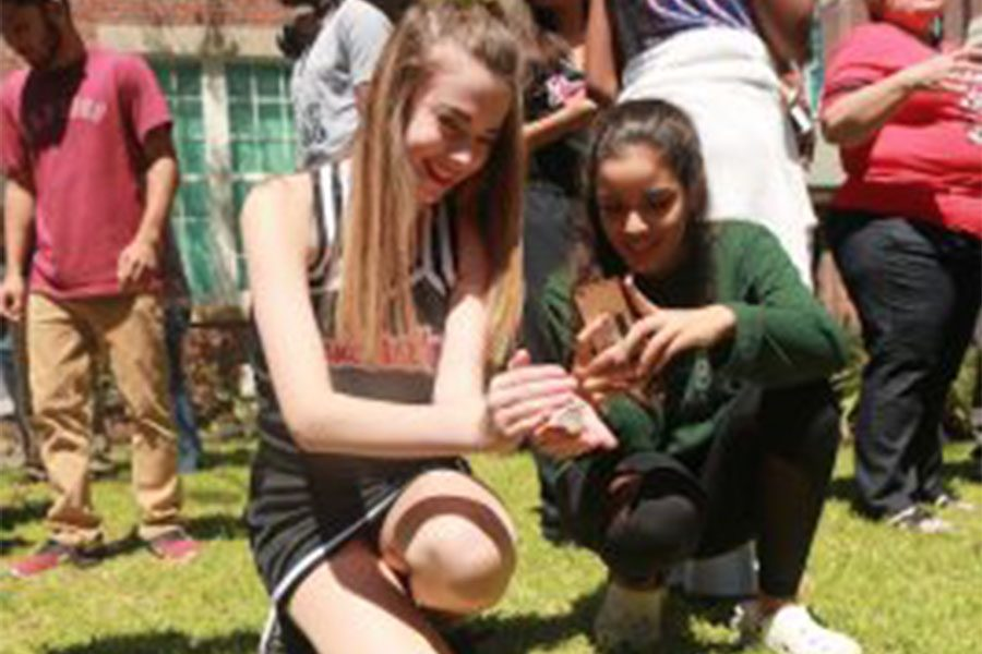 Freshman Olivia Sewell holds a butterfly in her hands for a picture.