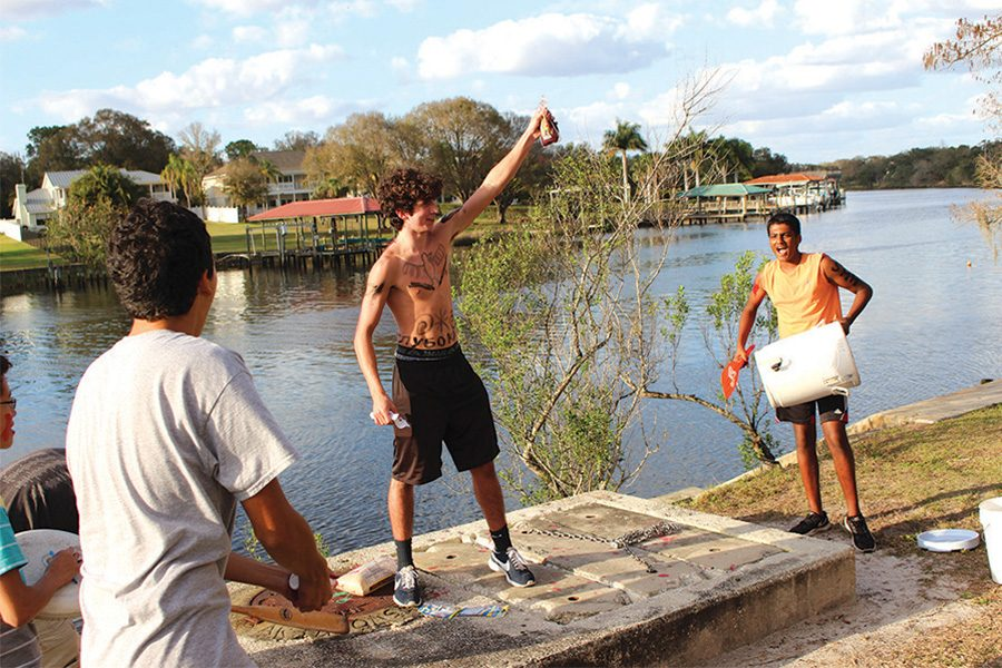 Junior Luis Cuevas prepares the crowd for the sacrifice while freshman Vivek Kondapavuluru beats on a water cooler.
