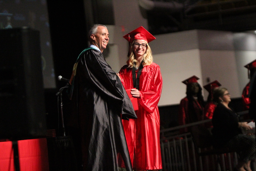 Jenika Freeman poses with Principal Gary Brady for a photo as she accepts her diploma cover.
