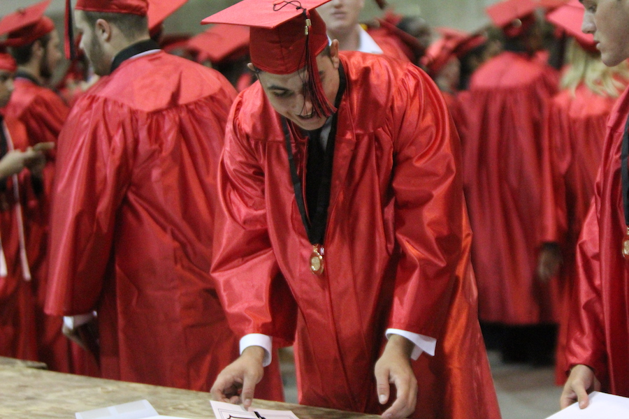 After the ceremony, Nick Romano places his diploma into its cover.