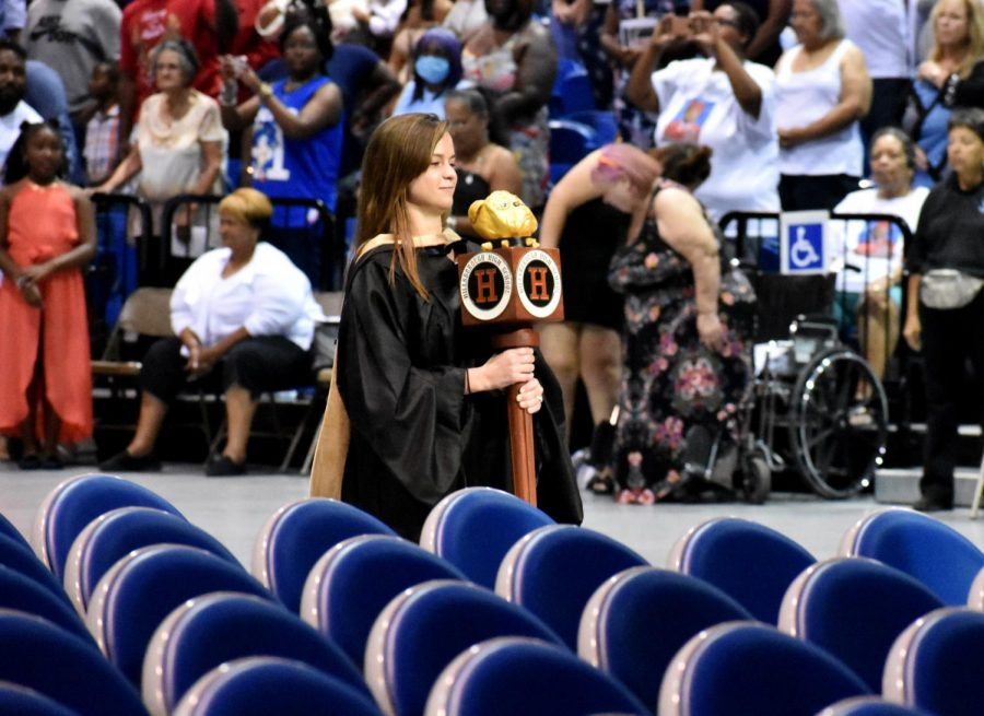 Stefanie+Zimmerman+enters+graduation+with+the+Hillsborough+High+School+terrier+scepter.+This+has+been+an+ongoing+tradition+at+each+graduation.+It+is+placed+in+front+of+the+stage+before+the+graduates+enter.+