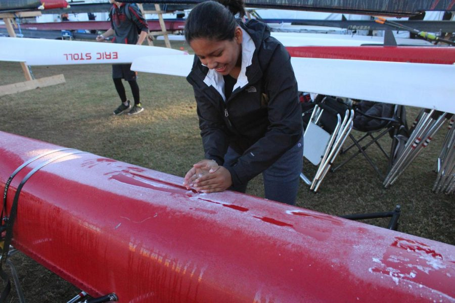 Sophomore Gabriella Sprague plays with frost that formed on the boats. Temperatures got below freezing on the night before the first day of the Head of the Hooch Regatta.
