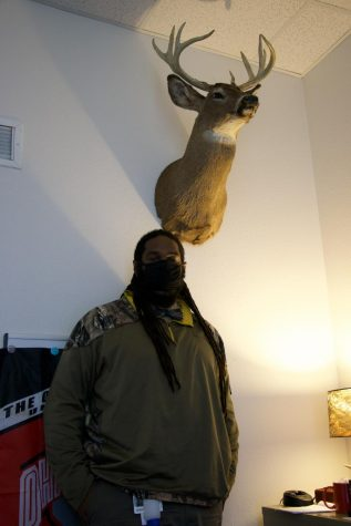 Travian Mitchell poses next to the taxidermied deer head in his office.
