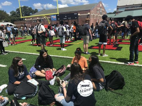 Students crowd on the football field during the alarm. Some choose to make the best of it and continue with their lunch.